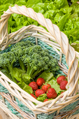 Basket of freshly harvested broccoli, lettuce and strawberries, resting beside a lettuce garden