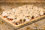 Homemade meat and veggie pizza with toppings of sausage, pepperoni, canadian bacon, black olives, mushrooms, mozzarella cheese, parmesan cheese and romano cheese, ready to bake