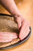 Once the pizza dough has been stretched as much as possible in the air, flatten it with your hands, starting at the center and working outwards, use your fingertips to press the dough until it will not stretch further.