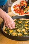 Woman placing sauteed summer squash on top of the multi-grain pizza with pesto sauce