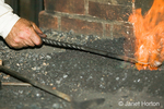 Blacksmith hand-holding iron piece going in for the heat