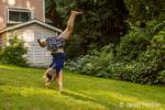 Seven-year old girl doing cartwheels in the backyard