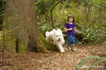 Five month old Goldendoodle, Chinook, running together with a four year old girl on their backyard trail