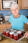 Woman holding her jars of home-canned raspberry jam which have cooled for 24 hours and are now ready to be put into the freezer