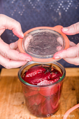 Woman placing a lid on a Weck canning jar of beets and pickling solution.