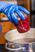 Woman placing a Weck canning jar of beets in pickling solution into a hot water bath.