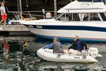 Couple coming into the marina in their inflatable boat from their sailboat anchored in the harbor, in Roche Harbor