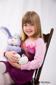 Five year old girl sitting in a wood rocking chair holding a stuffed rabbit