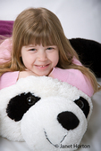 Five year old girl cuddling with a giant, stuffed panda bear