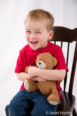 Three year old boy hugging teddy bear while sitting in rocking chair