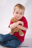 Three year old boy hugging teddy bear