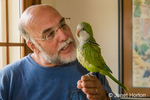 Man holding and talking to a Monk parakeet
