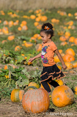 Self-confident young girl running through a pumpkin patch at The Gorge White House Fruit Stand