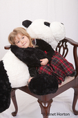 Four year old girl resting on giant stuffed panda bear