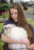 Young woman holding pet rabbit (half purebred Angora and half purebred french lop) in front yard