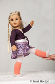 American Girl doll getting a little help from her teacher to do one of her stretches in dance class