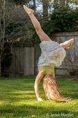 Seven year old girl doing a cartwheel in her backyard