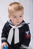 Two year old boy in sailor outfit holding his favorite rubber ball