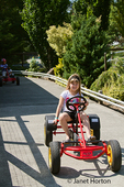 Six year old girl riding a pedal car