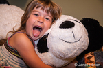 Four year old girl with tongue out, hugging stuffed panda bear