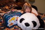 Four year old girl hugging stuffed panda bear that she's going to sleep with while staying at her Grandma's house