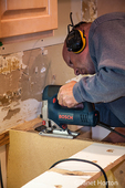 Man using a jig saw to refine the hole size for the kitchen sink during a kitchen remodel