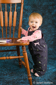 10 month old girl standing by a chair, playing with her toys