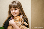Seven year old girl cuddling with her pet cat