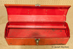 Empty, red, well-used toolbox on an old workbench