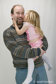 Father holding 3 year old daughter who is giving him a big kiss