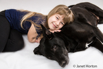 Seven year old girl resting her head on her labrador mix dog, Norbert