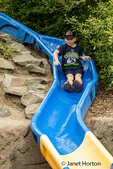 Seven year old boy going down a slide in the kids play area at the Woodland Park Zoo in Seattle, Washington, USA