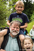 Seven year old boy getting a piggyback ride from his grandfather, with his nine year old sister getting into the fun too, at the Woodland Park Zoo in Seattle, Washington, USA