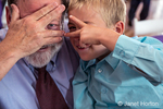 Seven year old boy and his 67 year old grandfather partially hiding their faces at a wedding in Seattle, Washington, USA