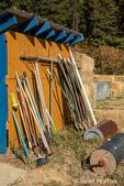 Toolshed with a variety of garden tools including rakes, brooms, stakes, and rollers, in Leavenworth, Washington, USA