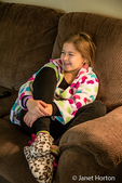 Ten year old girl in robe and pajamas sitting on a sofa watching TV in Issaquah, Washington, USA