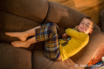 Looking down on a seven year old boy in pajamas lying on a sofa hugging his teddy bear, in Issaquah, Washington, USA