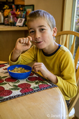 Seven year old boy in pajamas eating a bowl of cereal