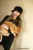 Ten year old girl looking surprised when her cat she is holding, scratches her, in Issaquah, Washington, USA