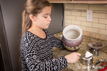 Ten year old girl measuring flour for use in making cookies in Issaquah, Washington, USA