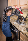 Ten year old girl playfully scraping the stiff ball of sugar cookie dough from the blades of the stand mixer in Issaquah, Washington, USA