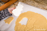 Ten year old girl using cookie cutters to cut out Christmas sugar cookies in Issaquah, Washington, USA