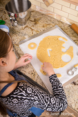 Ten year old girl removing the excess cookie dough from around the Christmas shapes that she has cut out using cookie cutters in Issaquah, Washington, USA
