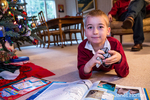 Seven year old boy reading his world atlas book and playing with toys he received for Christmas