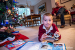 Seven year old boy reading his world atlas book and playing with toys he received for Christmas, with his father in the background reading a book