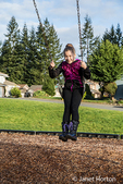 Ten year old girl on a swing in a playground in Issaquah, Washington, USA