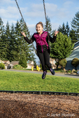 Ten year old girl swinging without hanging on in a playground in Issaquah, Washington, USA