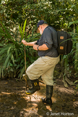 Man rinsing rubber boots after going for a hike in the tropical jungle around the Pachira Lodge
