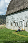 Man playing a banjo next to an old barn