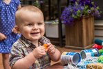 Fourteen month old happy toddler boy playing with a plastic carrot and other toys outside, using a spa cover for a table